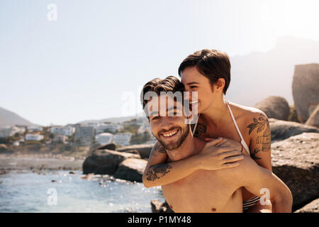 Man carrying woman on his back at the beach on a holiday. Tourist couple in a happy and romantic mood enjoying a holiday. - Stock Photo