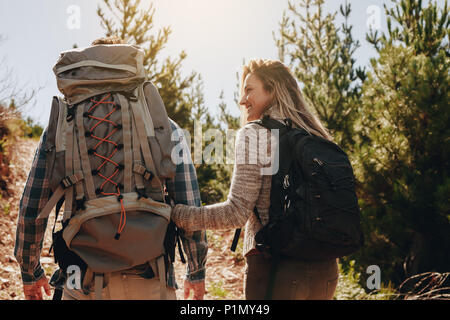 Rear view of couple of young people hiking. Young man and woman with their backpacks hiking on mountain. - Stock Photo