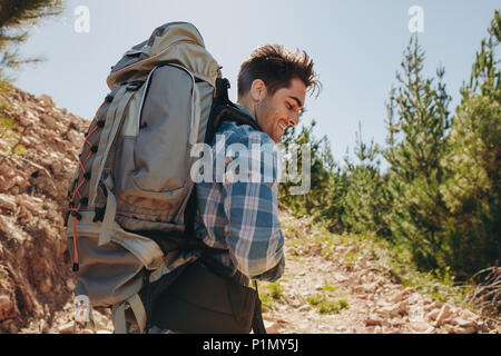 Rear view shot of smiling young guy with backpack hiking on mountains. Caucasian male hiker trekking on mountain. - Stock Photo