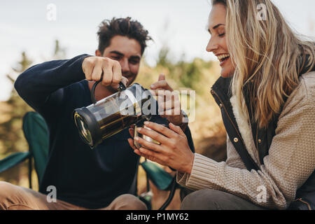 Young couple having coffee at a campsite. Man serving coffee to woman. - Stock Photo