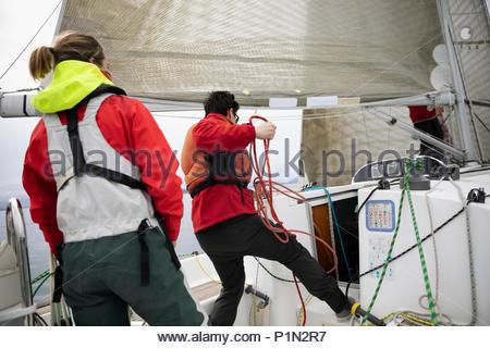 Sailing team adjusting rigging rope on sailboat - Stock Photo