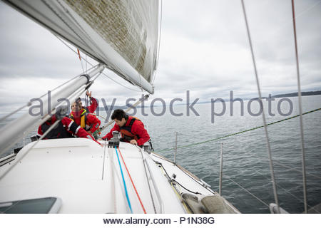 Sailing team training on sailboat on ocean - Stock Photo