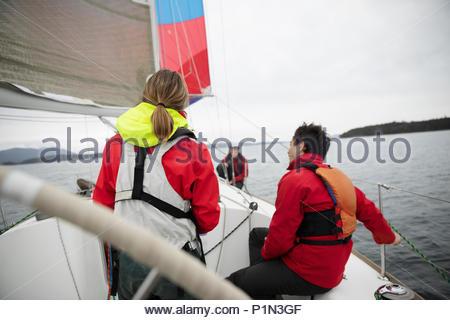 Sailing team training on sailboat on ocean - Stock Photo