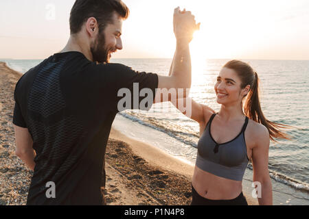 Happy young couple giving high five while standing at the beach - Stock Photo