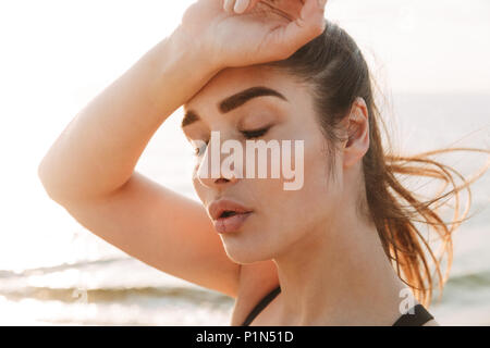 Close up portrait of an exhausted young sportswoman wiping forehead with her hand at the beach