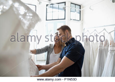 Bride and groom shopping for wedding dresses in bridal boutique - Stock Photo