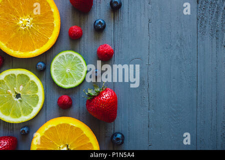 Blueberries, Raspberries, Strawberries, Oranges, Lemons and Limes on Blue Table with Space for Copy - Stock Photo