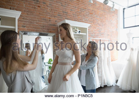 Bride and friends at wedding dress fitting in bridal boutique - Stock Photo