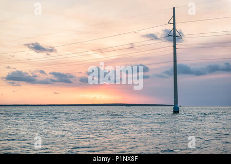 Sunset in Islamorada, Florida Keys, with pink sky, power lines, green water on gulf of Mexico, or Atlantic Ocean, horizon with sun, boat and island - Stock Photo
