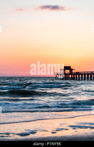 Naples, Florida pink and orange sunset vertical view in gulf of Mexico with sun setting inside Pier wooden jetty, horizon and dark blue ocean waves - Stock Photo