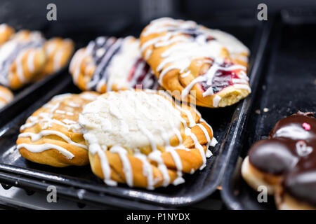 Closeup of many yellow cream cheese berry fruit icing drizzled baked danish pastries on shelf tray display desserts in bakery shop cafe store - Stock Photo