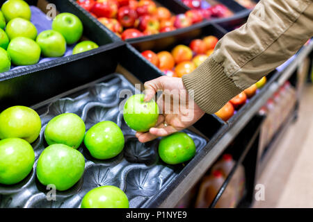 Green assorted apples on display shelf in grocery store boxes in aisle, supermarket inside, man person customer touching with hand holding granny smit - Stock Photo