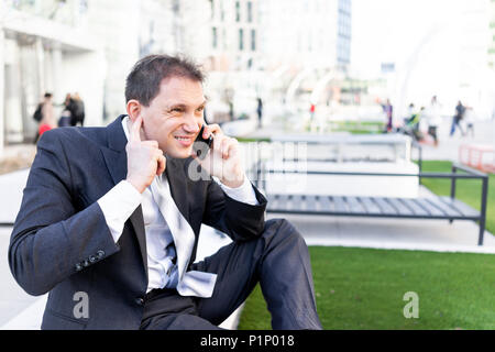 Funny businessman sitting on bench making face hearing impaired talking holding smartphone phone mobile cellphone in suit and tie on interview break i - Stock Photo