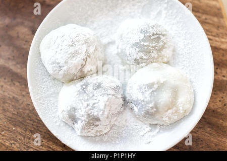 Four round whole mochi sticky glutinous rice cake dessert pieces, wagashi daifuku filled with ice cream or red bean adzuki jam filling - Stock Photo