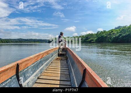 Man piloting a transport canoe on the Napo River Ecuador - Stock Photo