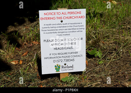 Notice in the churchyard, warning visitors that some headstones are unsafe, England UK - Stock Photo
