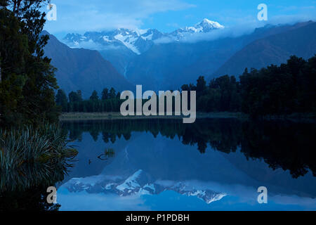 Summits of Mt Tasman (left) and Aoraki / Mt Cook (right) reflected in Lake Matheson, Westland National Park, West Coast, South Island, New Zealand - Stock Photo