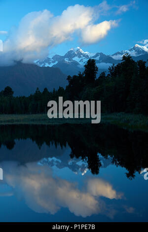 Summits of Mt Tasman (center) and Aoraki / Mt Cook (right) reflected in Lake Matheson, Westland National Park, West Coast, South Island, New Zealand - Stock Photo