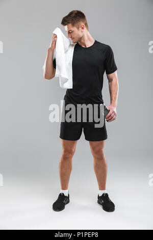 Full length portrait of a focused young sportsman wiping face with a towel and holding water bottle isolated over gray background - Stock Photo