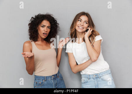 Portrait of two pretty young women standing together, smiling woman talking on mobile phone isolated over gray background - Stock Photo