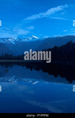 Summits of Mt Tasman (left) and Aoraki / Mt Cook (center) reflected in Lake Matheson, Westland National Park, West Coast, South Island, New Zealand - Stock Photo