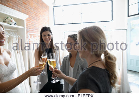 Bride, mother and friends toasting champagne at wedding dress fitting at bridal boutique - Stock Photo