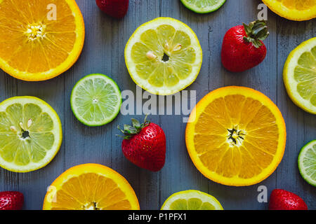 Mixed Sliced Oranges, Lemons and  Limes with Strawberries on Blue Table - Stock Photo