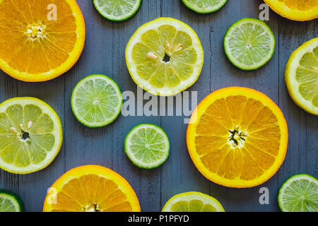 Mixed Sliced Oranges, Lemons and Limes on Blue Table - Stock Photo
