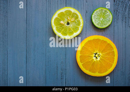 Orange, Lemon and Lime Slice on Blue Table with Copy Space - Stock Photo