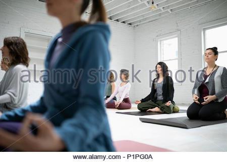 Women sitting in lotus position meditation in yoga class - Stock Photo