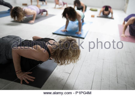 Women practicing yoga plank pose in yoga class - Stock Photo
