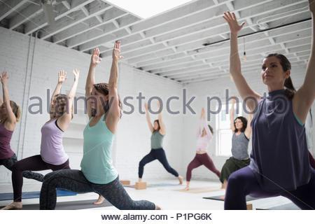 Women practicing yoga warrior one pose in yoga class - Stock Photo