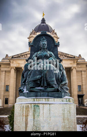 A sculpture of Queen Victoria with the Manitoba Legislative Building in the background with a statue of the Golden Boy on top - Stock Photo