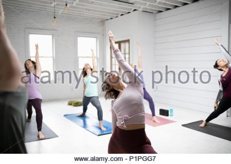 Women practicing yoga reverse warrior pose in yoga class - Stock Photo