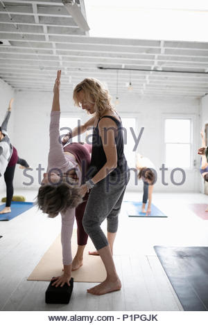 Yoga instructor helping woman practicing half moon pose in yoga class - Stock Photo