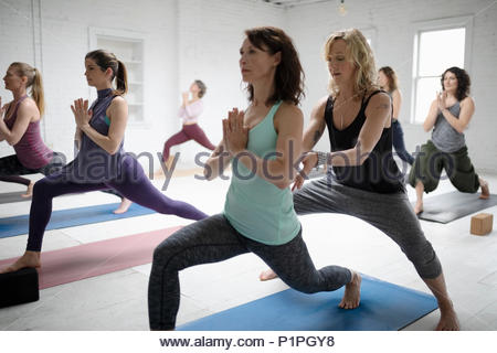 Yoga instructor guiding woman practicing warrior one pose - Stock Photo