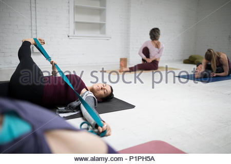 Woman practicing yoga lying leg crossover stretch with strap in yoga class - Stock Photo