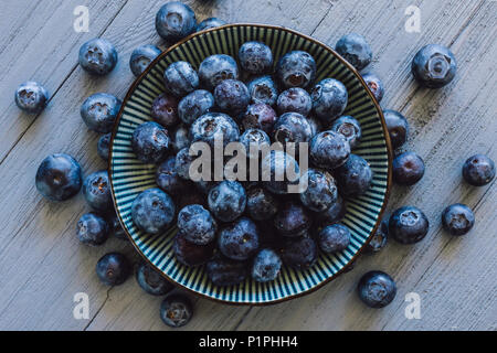 Centered Bowl of Blueberries with Scattered Berries on Blue Table - Stock Photo