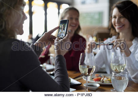 Women friends with camera phones eating sushi and drinking wine at restaurant - Stock Photo