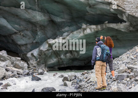 A woman takes a photograph of an ice cave with her cell phone while hiking to Gulkana Glacier with her husband; Alaska, United States of America - Stock Photo