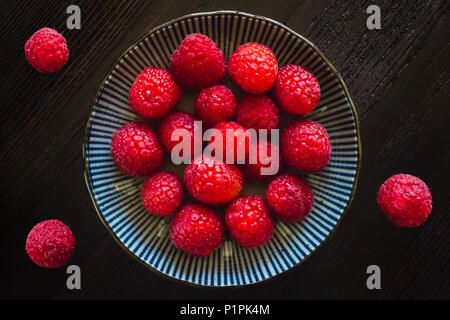 Fresh Raspberries in Bowl and on Dark Wood Table - Stock Photo