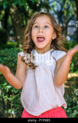 Cute five years old little girl with blue eyes and blond hair showing happiness and surprised on her face with a park as background - Stock Photo