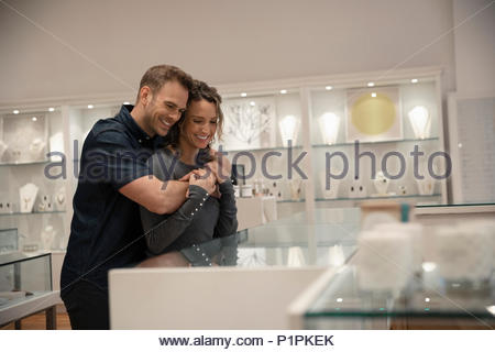 Affectionate couple shopping for jewelry at display case in boutique - Stock Photo