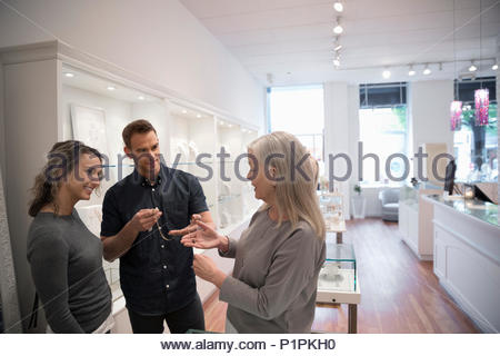 Jewelry boutique owner helping couple chopping for necklace - Stock Photo