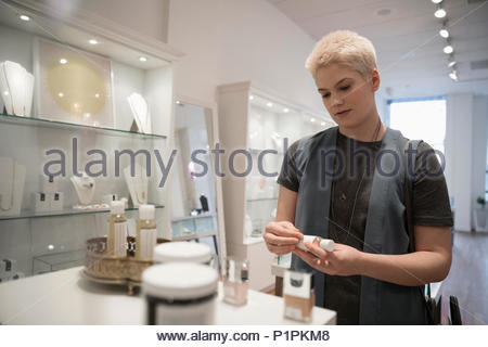 Young woman shopping for beauty products in boutique - Stock Photo
