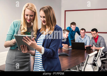 Two young millennial business professionals looking at a tablet while working together in a conference room with their peers - Stock Photo