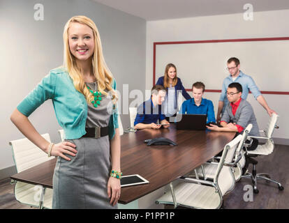A beautiful young millennial business woman working on her tablet in a conference room with her co-workers; Sherwood Park, Alberta, Canada - Stock Photo