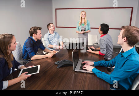 Young millennial businesswoman speaking to a group of young professionals in a conference room in a place of business; Sherwood Park, Alberta, Canada - Stock Photo