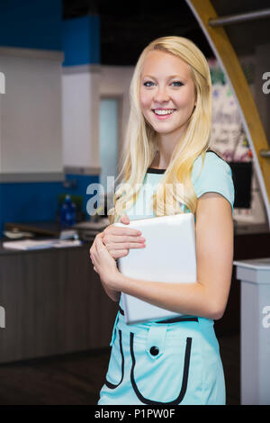 Beautiful young millennial business woman with long blond hair posing for the camera in the workplace; Edmonton, Alberta, Canada - Stock Photo