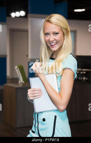 Beautiful young millennial business woman with long blond hair posing for the camera in the workplace, giving a sign of success - Stock Photo